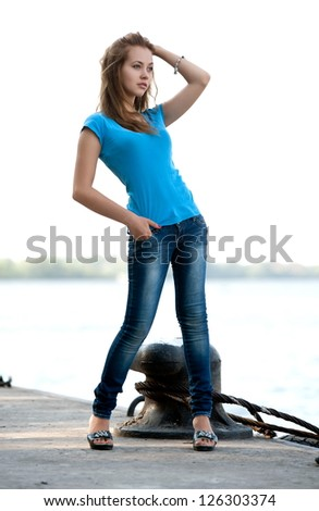 Beautiful brunette girl posing on berth - stock photo