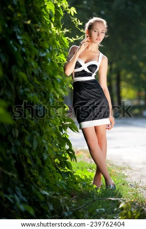 Beautiful brunette girl posing on the alley in the park - stock photo