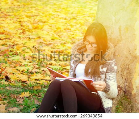 Beautiful brunette girl reading book in nature - stock photo