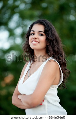 Beautiful brunette girl relaxing in the park wth many plants of background - stock photo