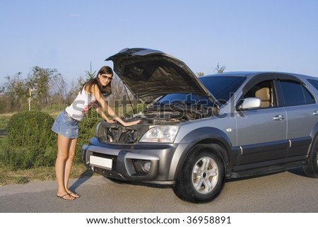 beautiful brunette girl repairing the car - stock photo