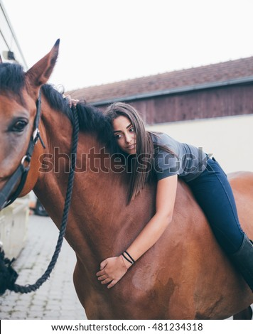 Beautiful brunette girl riding and hugging her horse. Selective focus on girl.