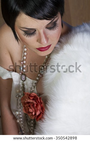 beautiful brunette girl 20s style flapper with jewels and white fur - stock photo