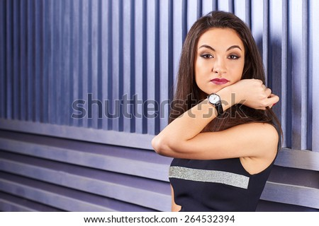 Beautiful brunette girl showing wrist watch. Demonstration of mechanical watches with leather strap. Automatic Watch. Time is money.  - stock photo