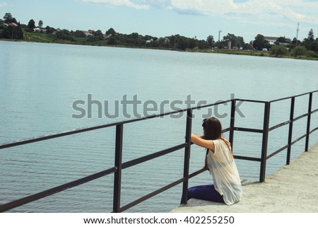 beautiful brunette girl sitting alone on a pier and looking at water in summer vacation