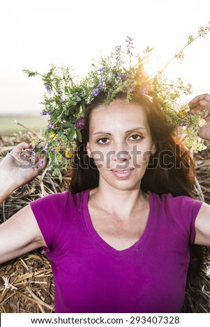 beautiful brunette girl stand near haystack with wreath from summer flowers against sunset sky Sun above head Cute woman outdoor on nature background Empty space for inscription  - stock photo