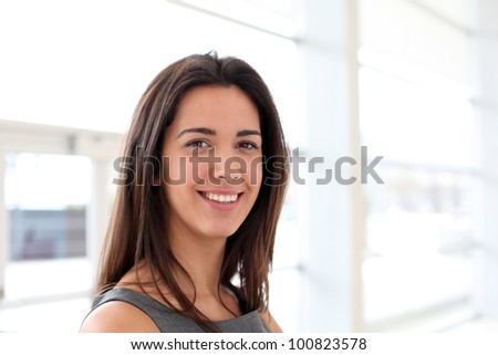 Beautiful brunette girl standing in hall - stock photo