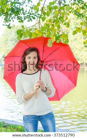 Beautiful brunette girl standing on the river bank under the open umbrella