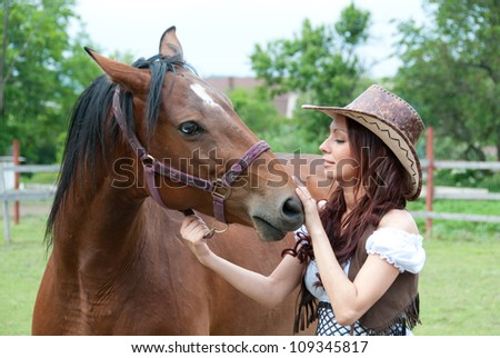 Beautiful brunette girl stroking a horse