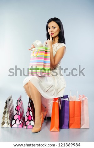 Beautiful brunette girl taking out her present from shopping bag - stock photo
