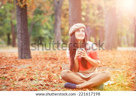 Beautiful brunette girl with cup in the park.