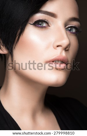 Beautiful brunette girl with evening make-up and perfect skin. Beauty face. Picture taken in the studio on a black background. - stock photo
