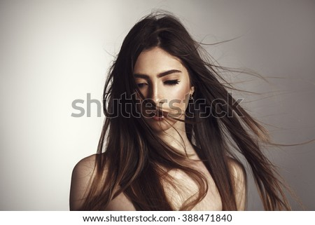 beautiful brunette girl with fluttering hair on wind. Glamour vogue style photoshoot.