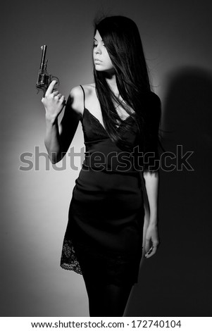 Beautiful brunette girl with fluttering hair with a revolver on a dark background. - stock photo