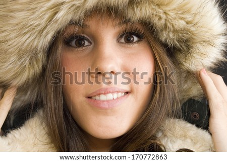 Beautiful Brunette Girl with fur cap over black background
