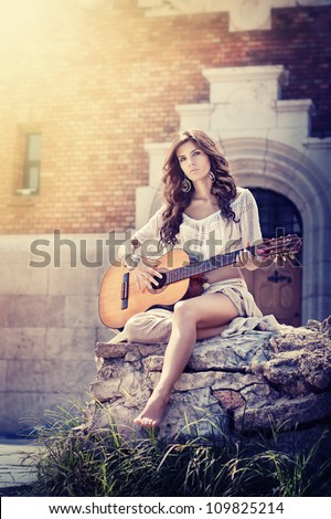 Beautiful brunette girl with guitar sitting on a rock in urban setting.