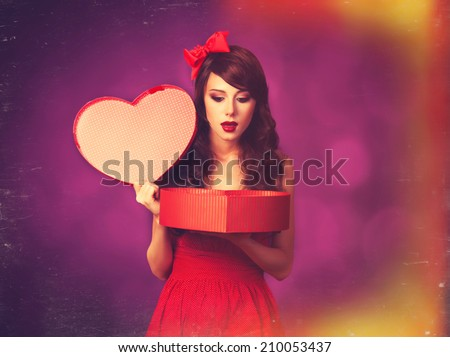 Beautiful brunette girl with heart shape gift on violet background.