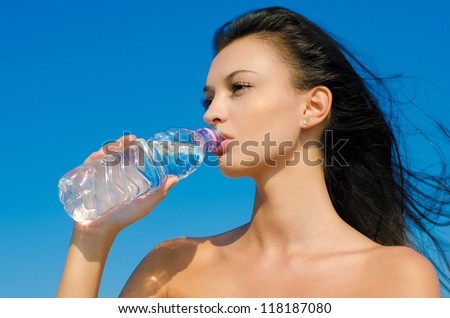Beautiful brunette girl, with long hair in the wind, drinking from a bottle of water. Outdoors, blue sky background.