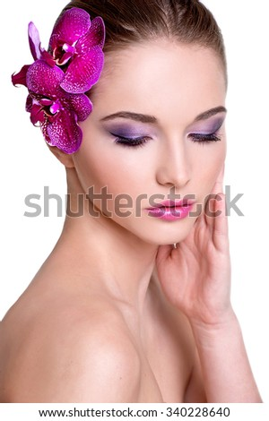 Beautiful brunette girl with orchid flowers - stock photo