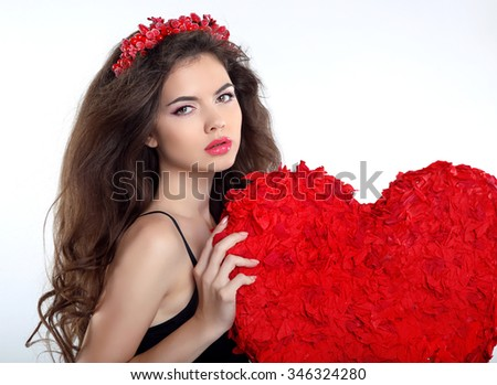 Beautiful brunette girl with red heart gift for Valentines Day. Beauty portrait of young woman with chaplet isolated on white background. - stock photo