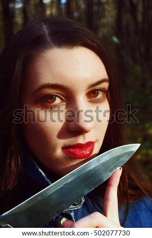 Beautiful brunette girl with red lips, dressed in the denim jacket, holding the knife as serial killer.Retro horror movie style, the photo is filtered.