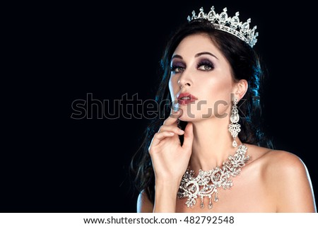 Beautiful brunette girl with silver crown, earrings and professional evening make-up. Beauty face. Luxurious woman with great expensive jewelry, white necklace. Sparkle and brilliance of diamonds.