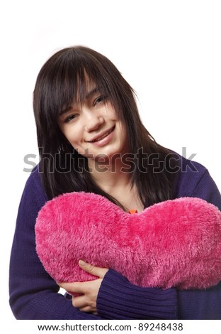 Beautiful brunette girl with toy heart. Photo for st. Valentine post card.