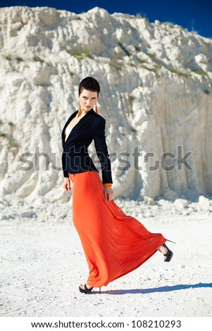 Beautiful brunette girl with trendy makeup and fashionable clothes posing in a rock. Summer.