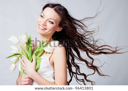 Beautiful brunette girl with white tulip flowers in studio