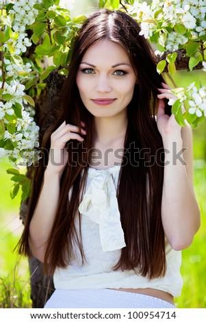 Beautiful brunette hair girl in blossom garden - stock photo
