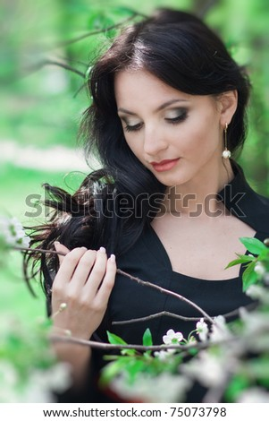 Beautiful brunette holding a blossoming cherry branch, Spring