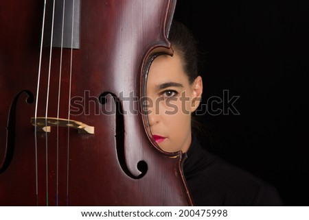Beautiful brunette holding a cello with selective light in black dress - stock photo
