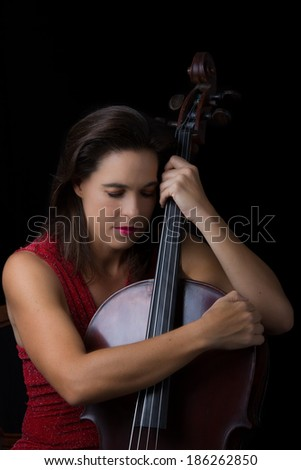 Beautiful brunette holding a cello with selective light in red dress