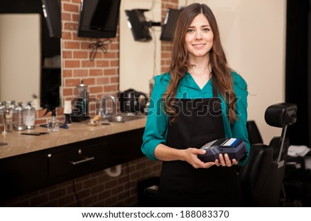 Beautiful brunette holding a credit card terminal in front of a barber shop and smiling - stock photo