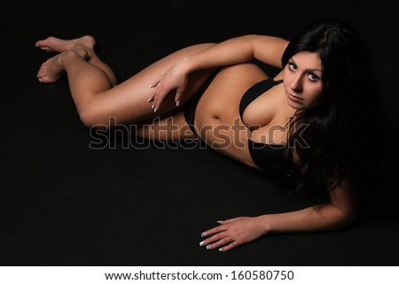 Beautiful brunette in a black underwear lying on the black background, in the studio, glamour photography
