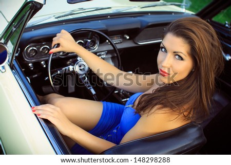 Beautiful brunette in a blue dress sits in the car, cabriolet, Pin Up style, fashion photography - stock photo