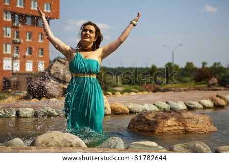 beautiful brunette in a blue dress standing in the water and throws the water up - stock photo