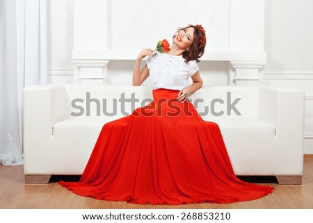 Beautiful brunette in a red skirt and a wreath sitting on a white couch and smiling broadly. - stock photo