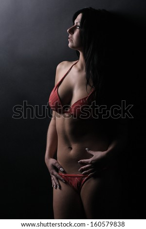 Beautiful brunette in a red swimsuit posing on the black background, in the studio, glamour photography