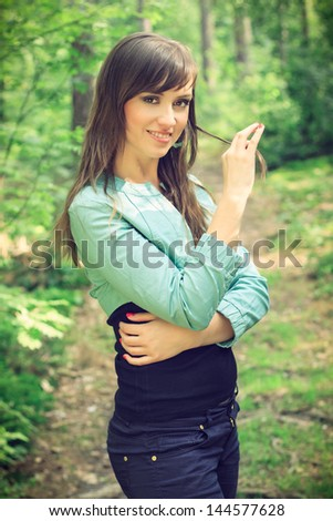 Beautiful brunette in a shirt and jeans posing on a forest road, in a nature, fashion photography