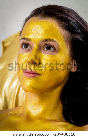 Beautiful brunette in a spa salon. Girl taking facial treatment at the salon. Facial treatment, gold mask, beauty, spa, mask - Concept of facial skin care. Article about koosmetologiyu.