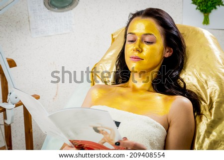 Beautiful brunette in a spa salon. Girl taking facial treatment at the salon. Facial treatment, gold mask, beauty, spa, mask - Concept of facial skin care. Article about koosmetologiyu. - stock photo