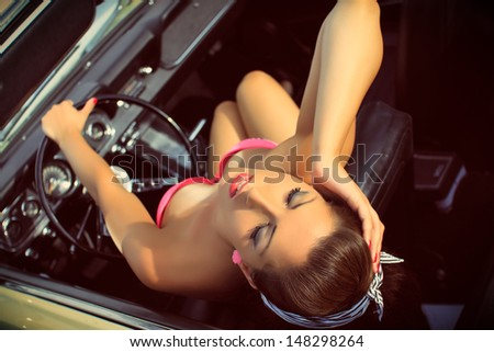 Beautiful brunette in a swimsuits sits in the car, cabriolet, Pin Up style, fashion photography