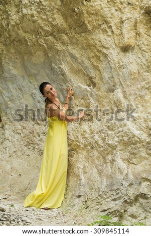 Beautiful brunette in a yellow dress. Brunette on a background of rock. Beautiful natural stone texture. Sincere emotions and good mood from posing for the camera. - stock photo