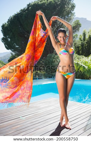 Beautiful brunette in bikini holding sarong up by the pool on a sunny day - stock photo