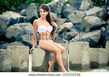 Beautiful brunette in bikini on the beach near stones - stock photo