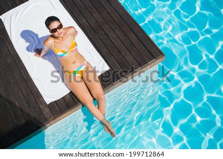 Beautiful brunette in bikini sitting by the pool looking up at camera on a sunny day - stock photo