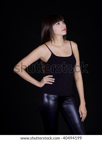 Beautiful brunette in black skin pants and a black shirt against a black background
