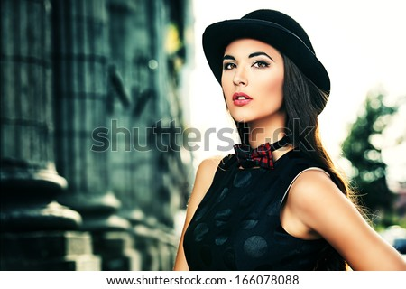 Beautiful brunette in bowler hat and bow-tie standing on the street of the old town. Retro style.