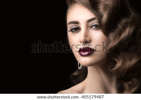 Beautiful brunette in  Hollywood manner with curls, dark lips. Beauty face.
